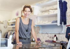 Mature saleswoman smiling while standing at the counter of a small store